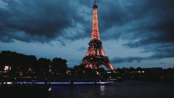 Eiffelova věž se rozsvítí v Paříži a lodě večer proplouvají řekou Seinou.