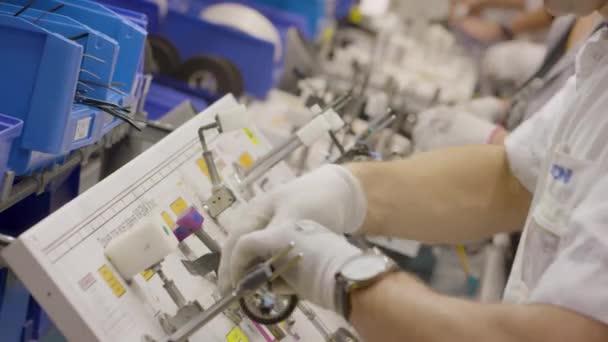 továrna na výrobu elektroinstalace automobilů. pracovník natočí pásku na dráty