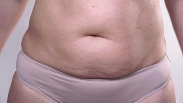 Žena středního věku s povislou pletí definuje své velké břicho a kroutí se na bílém pozadí.
