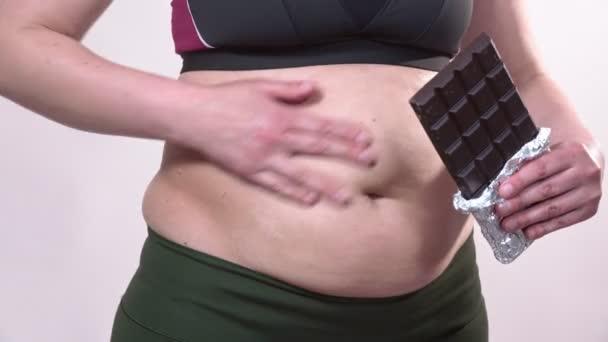Žena středního věku, která hladí povislý žaludek, ukazuje čokoládu. Na bílém pozadí.