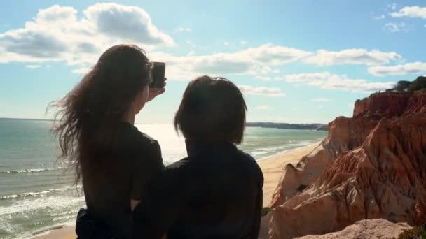 Erfolgreiche Frau mittleren Alters mit einem jungen Mädchen auf einer Klippe am Meer, Selfie mit dem Handy. Portugal. Vilamoura. Mutter mit Tochter.