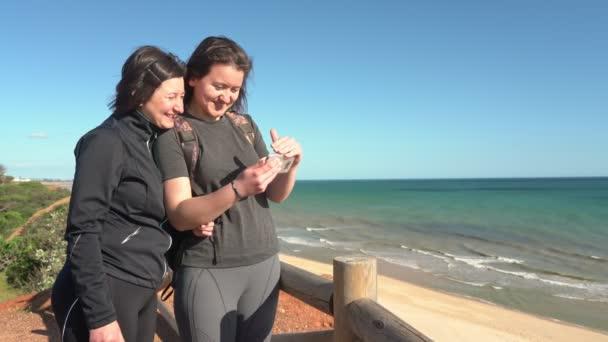 Erfolgreiche, glückliche Frau mittleren Alters mit einem jungen Mädchen auf einem Felsen am Meer lacht von dem, was er am Telefon gesehen hat. Portugal. Vilamoura. Mutter mit Tochter.