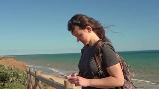 Erfolgreiches junges Mädchen auf einer Klippe in der Nähe des Ozeans, glücklich, schaut aufs Telefon.