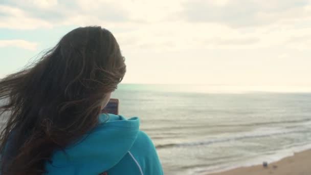 Junge Touristin am Strand am Meer mit dem Handy in der Hand fotografiert die Landschaft um ihn herum.
