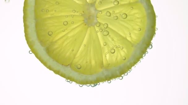 Das Konzept der Frische, eine Zitronenscheibe in klarem Wasser, mit erfrischenden Gasblasen, hautnah. Zitrusgetränke.