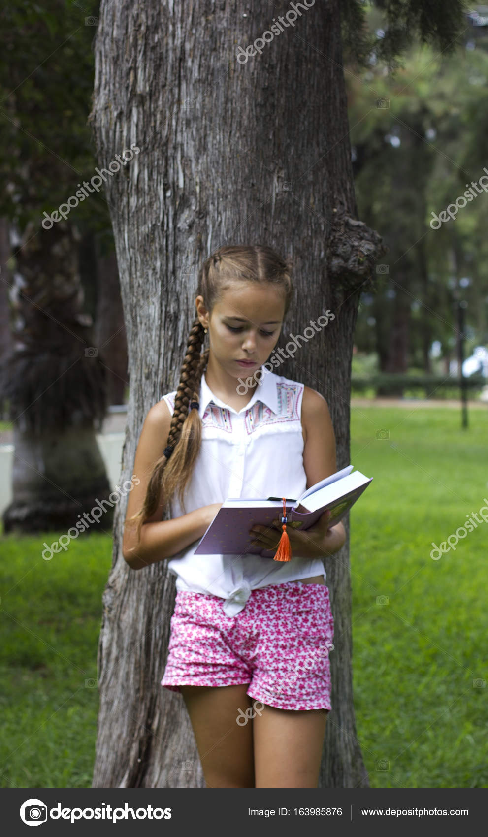 Young Teen Girl Reading Book Near The Pine Tree