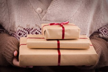 Gift boxes with red ribbon in the hands. Hands hold gifts in craft paper