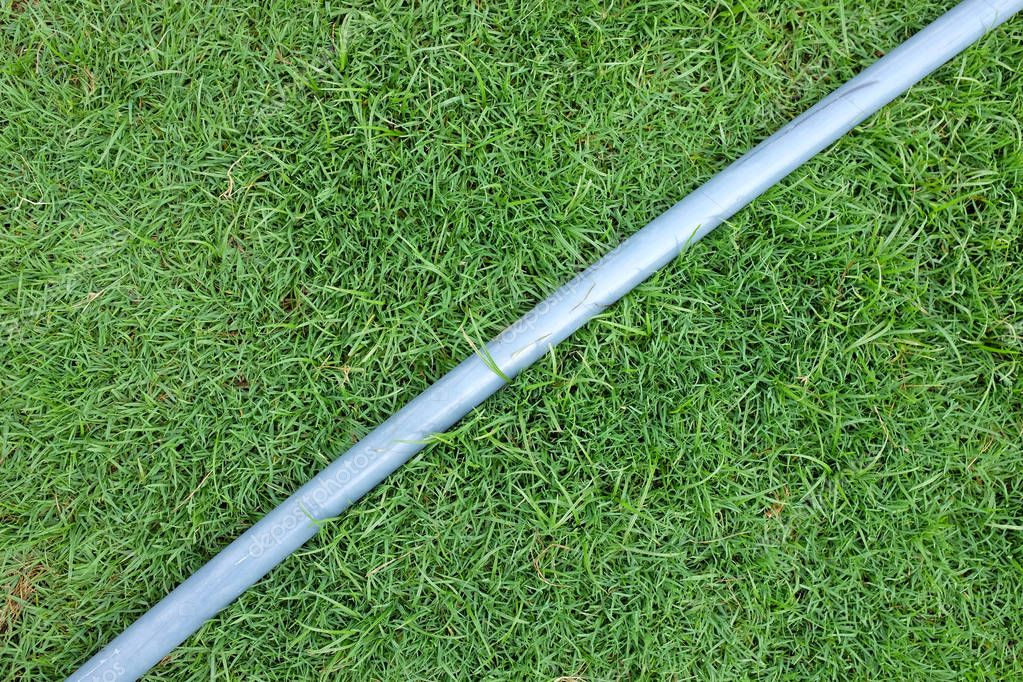 Water rubber tube lie on the green field.