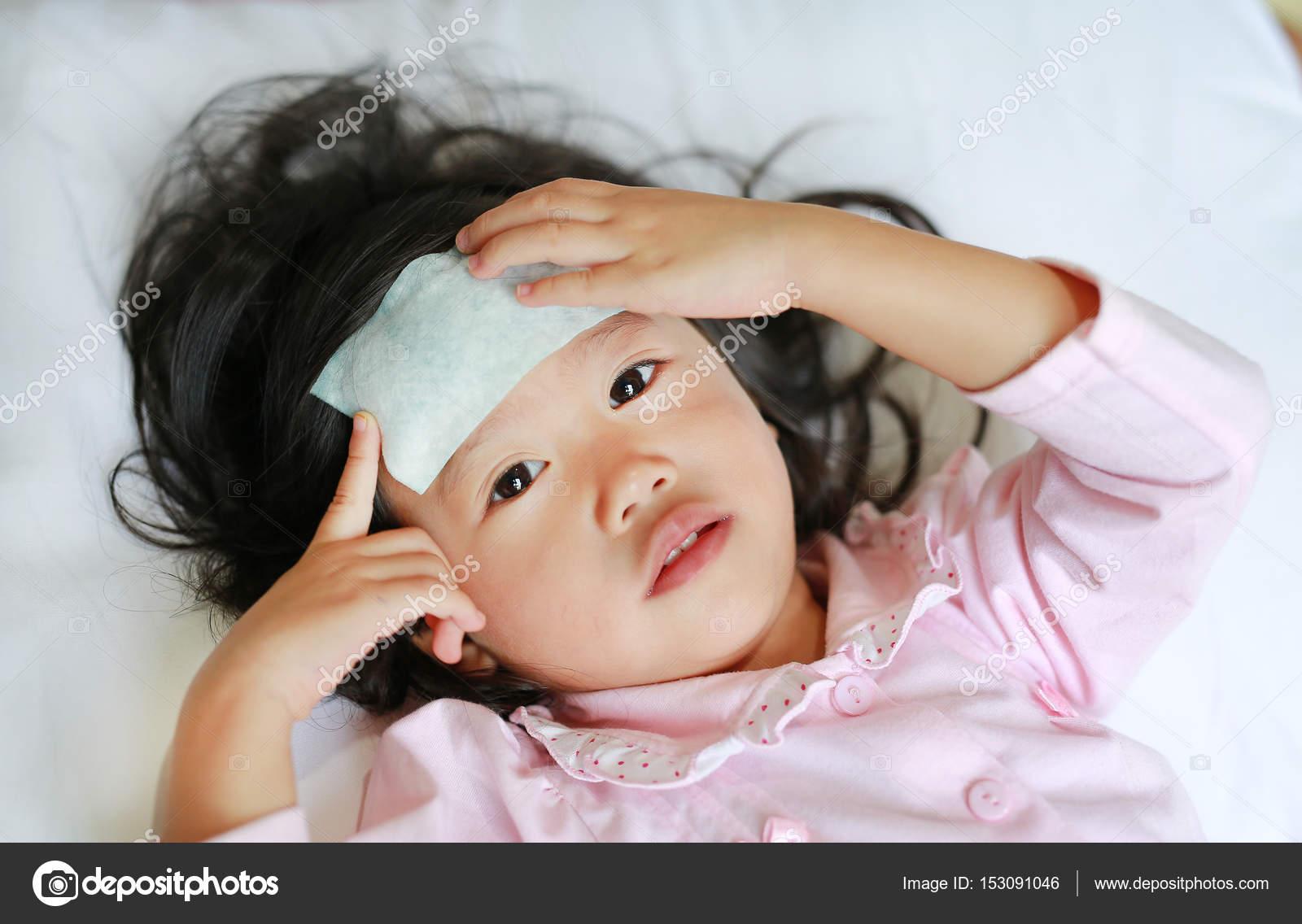 petite fille malade allong sur le lit avec un cool jell sur sa t te photographie civic dm. Black Bedroom Furniture Sets. Home Design Ideas