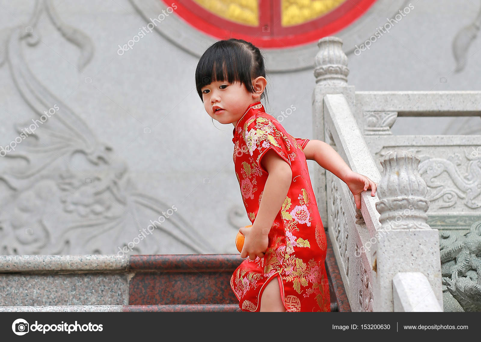 c9b0212824df3 Cute asian kid girl in Traditional Chinese dress with holding sacred Orange  at chinese temple in bangkok thailand, Chinese new year concept.