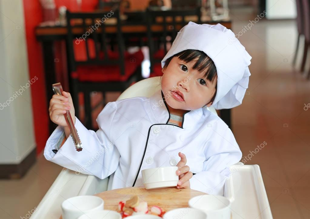 Kid girl in a suit of the little chef make mini pizza, Cooking child concept.