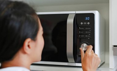 Woman using microwave oven at home.