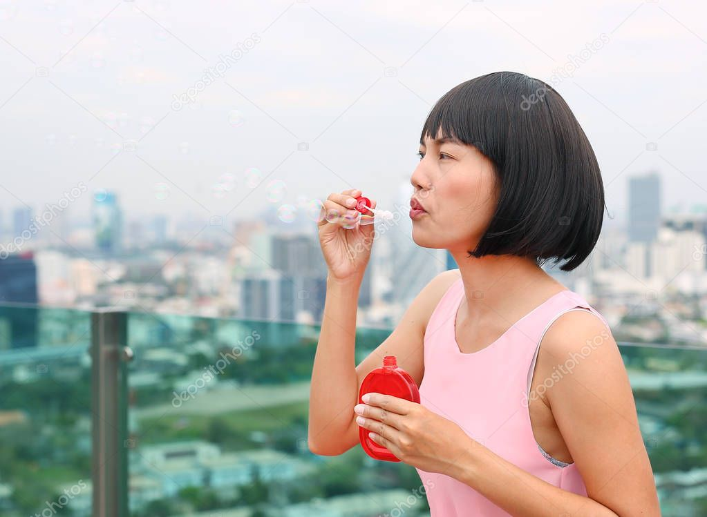 Young asian woman playing bubble on the roof top of building.