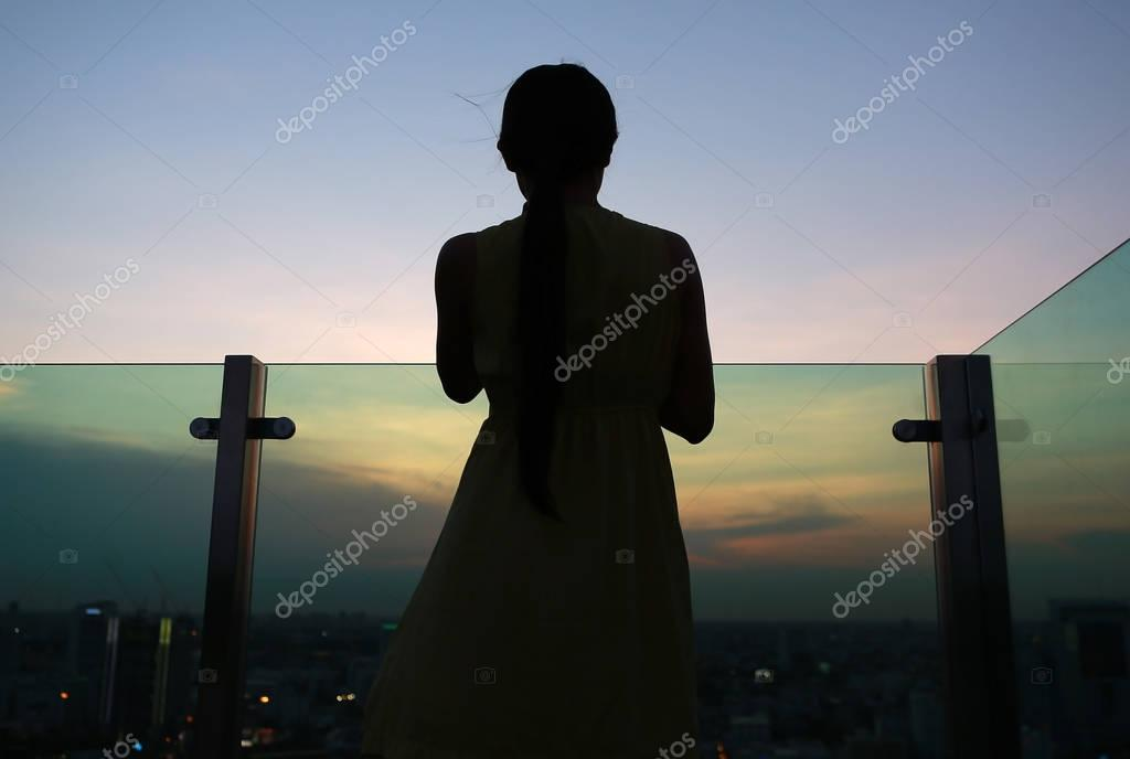 Silhouette of woman back facing the Sun at sunset on rooftop of the building