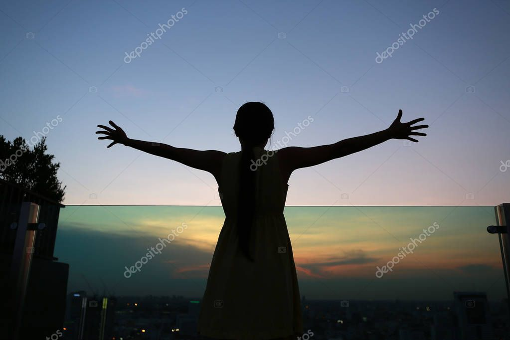 Silhouette of woman stretching arms enjoy relax at sunset on rooftop of the building