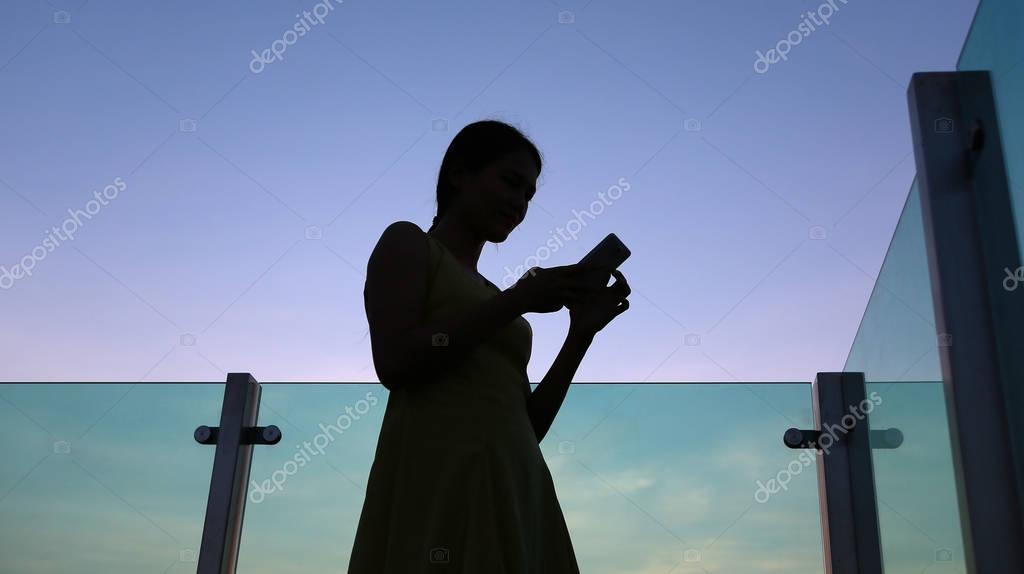 Silhouette of woman using smartphone at sunset on the rooftop of the building