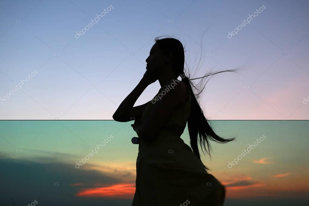 Silhouette of woman relax at sunset on rooftop of the building