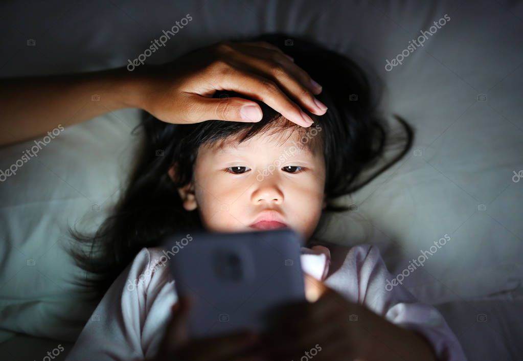 Cute little girl in pajamas playing smartphone lying on a bed with mother hand pat a head