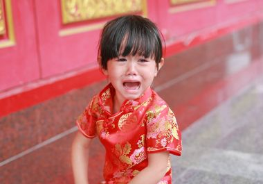 Cute little girl holding red packet monetary gift and crying at chinese temple in bangkok, Thailand.