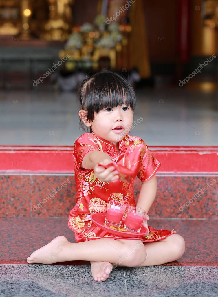 Asian child girl in traditional dress light the worship candles at chinese temple in bangkok, Thailand.