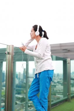 Young asian woman listening music in headphones at rooftop of the building. Happy relaxing girl