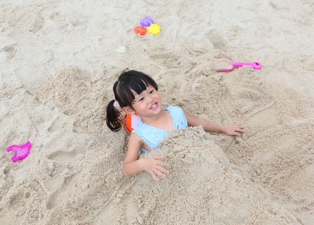 Cute child girl playing sand at the beach