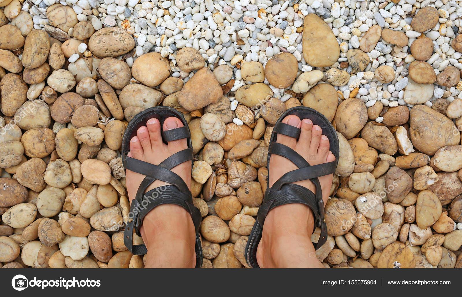 Blickte auf die Füße auf einer Schotterpiste, die Steinen im Garten ...