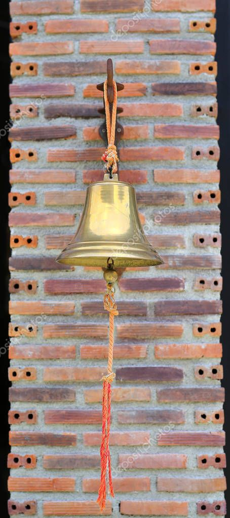 Brass bell hanging against brick pole