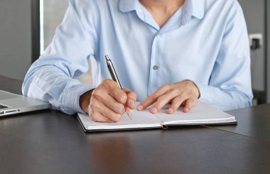 Close up young businessman sitting at the table on workplace in office is writing