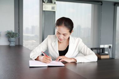 Young businesswoman sitting at the table on workplace in office and writing