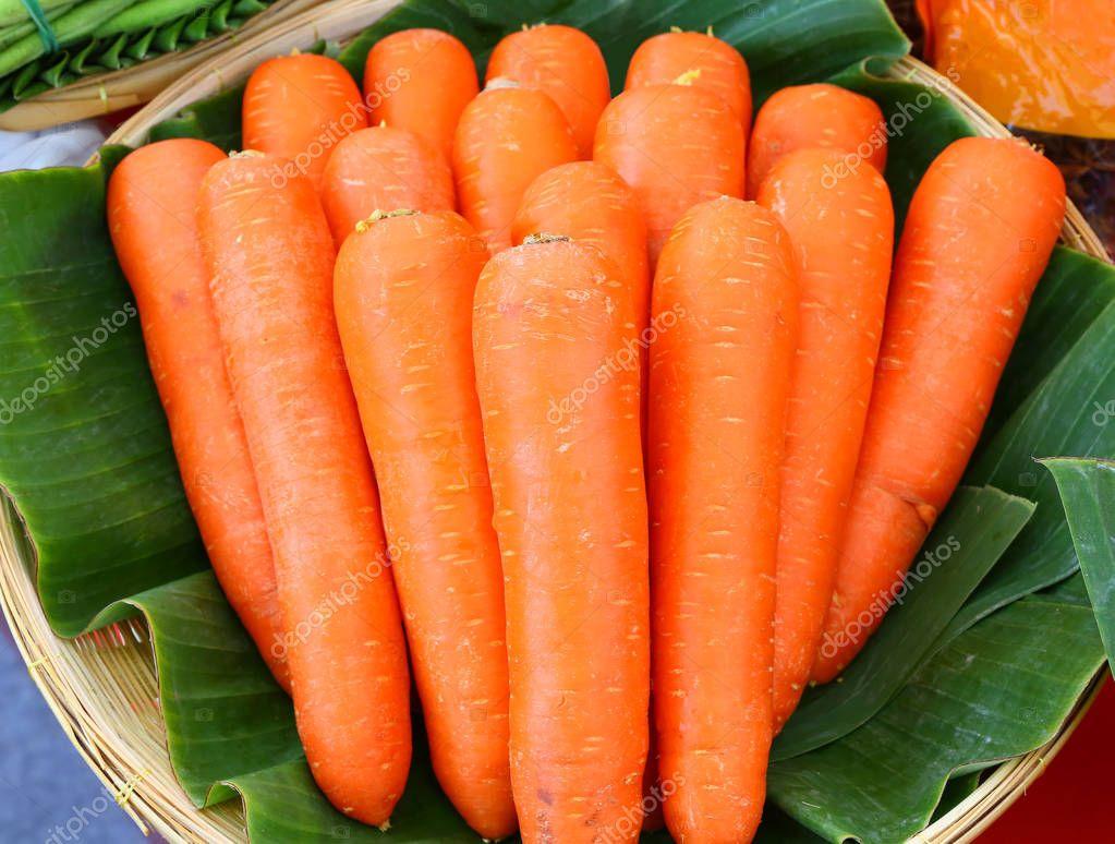 Fresh carrots in basket against banana leaf
