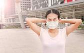 Frau trägt Schutzmaske, Umweltverschmutzung und die Grippe im öffentlichen Bereich zu schützen.