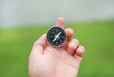 Compass in hand against nature background