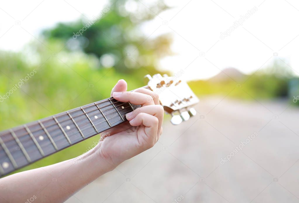Close-up male hand playing on acoustic guitar outdoor with rays of sunlight.