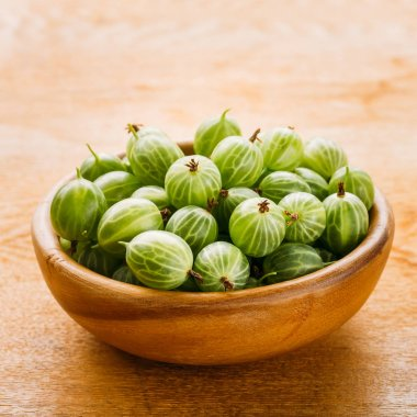 Close-Up Of Gooseberries In Vintage Wooden Bowl On Wooden Table