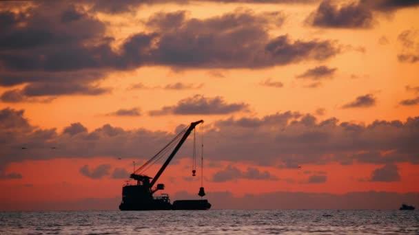 Západ slunce nad moře horizontu při západu slunce. Temná silueta rybářských lodí na obzoru scenérií. Přírodní Sunrise Sky teplé barvy přes oceán