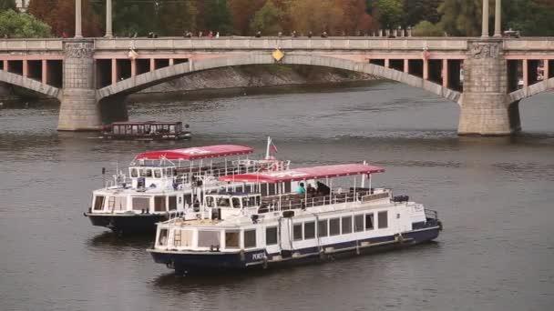 Praha, Česká republika. Pohled na Manes most a řeku Vltavu v podzimní den. Výletní lodě a vyhlídkové lodě plovoucí v řece Vltavě