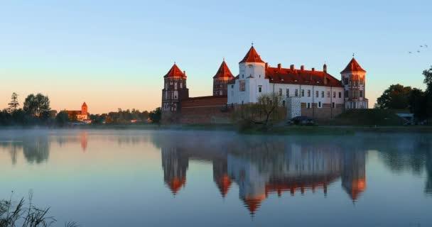 Mir, Bělorusko. Mir Castle Complex From Side Of Lake. Architektonický soubor feudalismu, starobylá kulturní památka, památka světového dědictví UNESCO. Slavná památka. Mlha nad jezerem v letním ránu