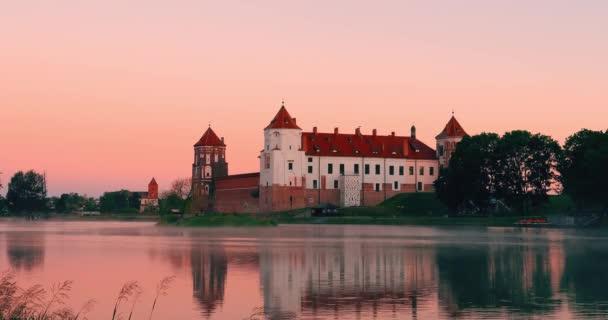 Mir, Bělorusko. Mir Castle Complex From Side Of Lake. Středověká kulturní památka, památka světového dědictví UNESCO. Slavný orientační bod v letním slunném večeru pod růžovým nebem. Mlha nad jezerem v létě