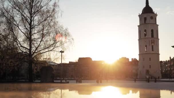Vilnius, Litva. Lidí, kteří jdou v náměstí poblíž Katedrála Basilica rákosem a St. Vladislav s zvonice v jarní Sunset