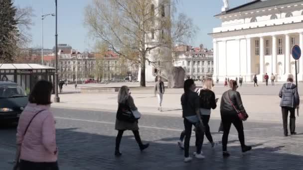 Vilnius, Litva. Lidí, kteří jdou v náměstí poblíž Katedrála Basilica rákosem a St. Vladislav s zvonice v jarní den