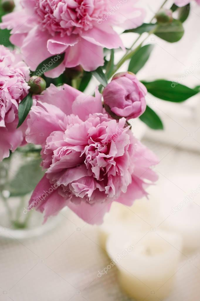 Pink peonies in a vase on a sill of  an old window