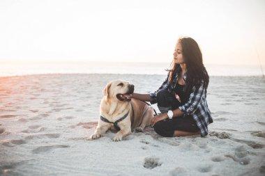 Girl sitting with dog on beach