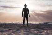 Fotografia Uomo in piedi sulla spiaggia sabbiosa