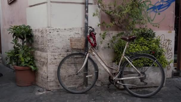 White vintage bicycle parked against wall of ancient European house, Rome, Italy