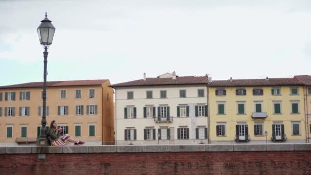 Frau sitzt auf Zaun neben Straßenlaterne und genießt italienisches Eis. Gesamtplan. Farbige Häuser sind auf dem Hintergrund