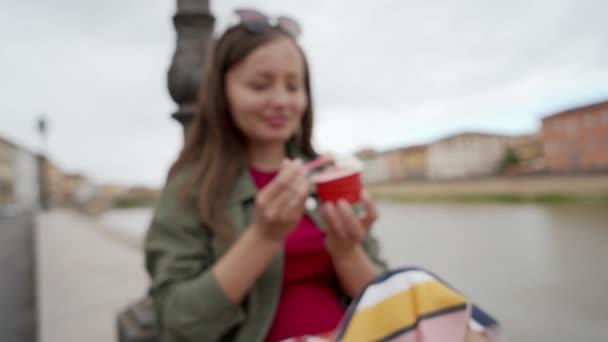 junge Frau genießt italienisches Eis auf der Promenade. junges Mädchen lächelt in die Kamera und zeigt Löffel mit leckerem Eis. verschwommener Hintergrund