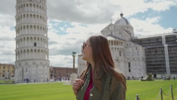 Smiling tourist girl with sunglasses walking near Leaning Tower of Pisa and exploring Piazza dei Miracoli on lovely day. Sightseeing. Famous landmark. Pisa, Italy