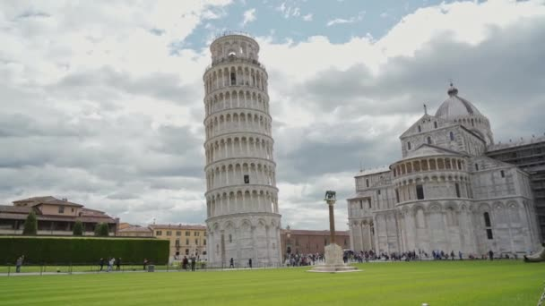 Tourist girl coming to Piazza dei Miracoli and looking with admiration at stunning Leaning Tower famous landmark. Rear view, Pisa, Italy