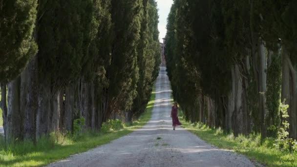 Žena v červených romantických šatech kráčí v dálce po stezce s cypřiši